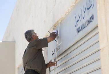 Calligrapher works on Crafts District signs at Raghadan Tourist Terminal